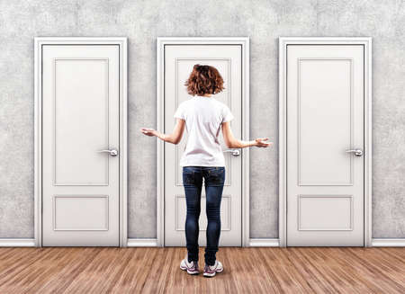 multiple choice: Girl before a white doors in fear of the unknown Stock Photo