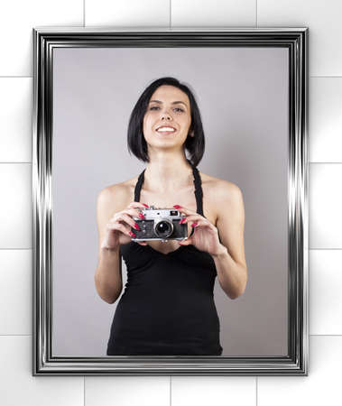 foto: Girl with camera is photographed before a mirror