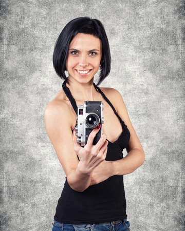 Beautiful girl stand with camera in hands photo