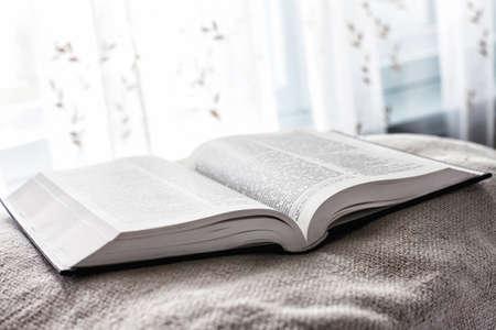 Foto der offenen Bibel in der Nähe eines Fensters Licht