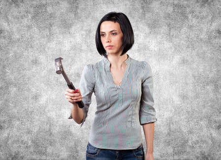 Beautiful girl with an iron hammer in a hand Stock Photo