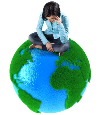 Sad girl sits on small planet Earth photo