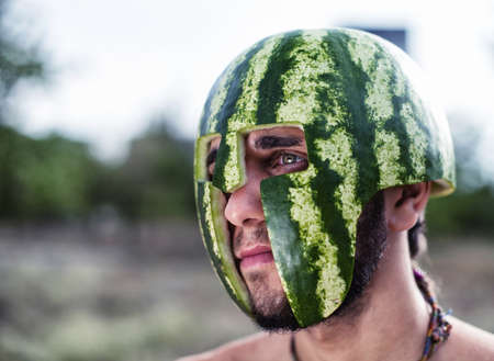 Photo of the young soldier with a water-melon on a head photo