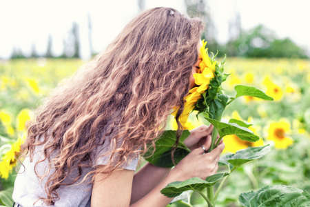 The beautiful girl smells a yellow sunflower photo