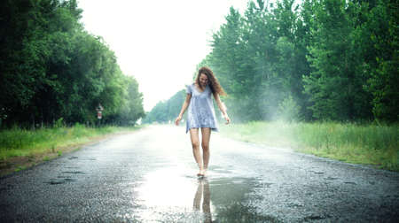 puddle: Beautiful girl jumps in a puddle on the road Stock Photo