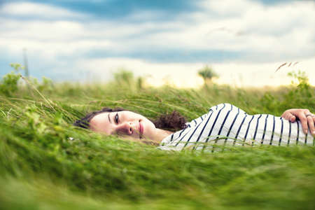 The young girl lies in a green grass photo