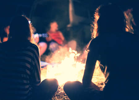 stories: People sit at night round a bright bonfire