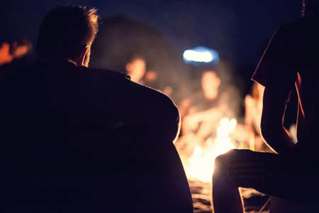 campfires: People sit at night round a bright bonfire