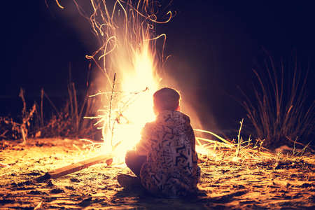Young boy sit near a bright bonfire Stok Fotoğraf