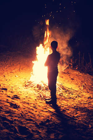 burning man: Young boy stand near a bright bonfire