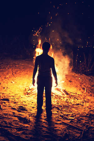 terribly: Young boy stand near a bright bonfire
