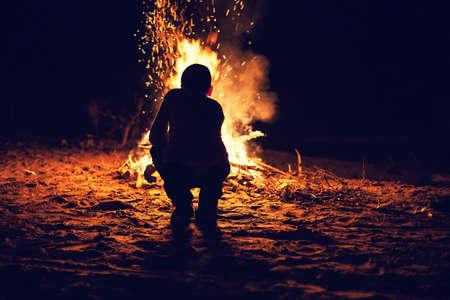 明るいのたき火の近くに少年座って 写真素材