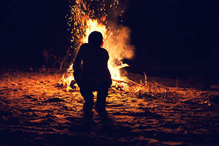 Young boy sit near a bright bonfire Stock Photo