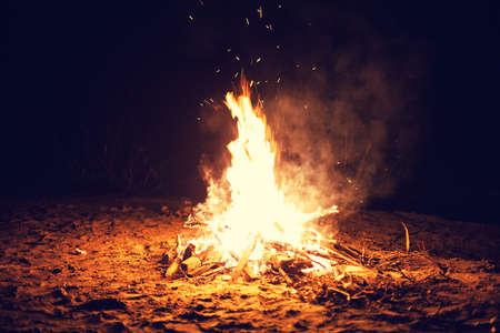 fogatas: Los brillantes grandes quemaduras hoguera en la playa en la noche