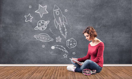 thinks: The girl with the computer dreams about cosmos Stock Photo