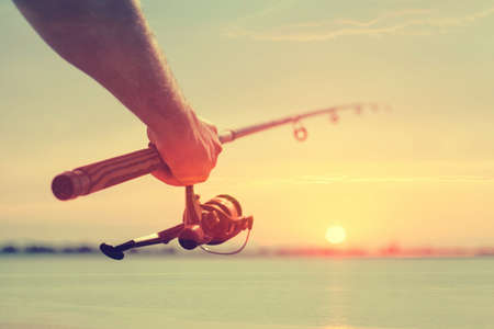 Hand with a fishing tackle against the beautiful sky photo