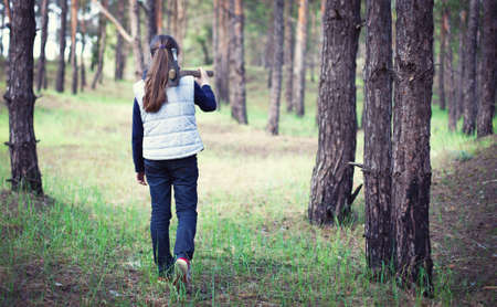 axe girl: The young girl walks on forest with axe