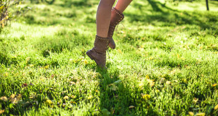tiptoe: Photo of feet of the girl walking on a grass