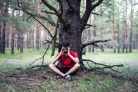under a tree: The young boy sits in fear under a tree