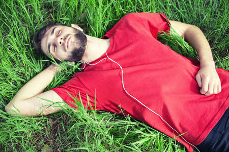 listens: The boy in a green grass listens to music
