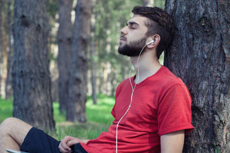 listens: The boy sits under a tree and listens to music