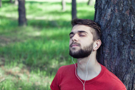 earphone: The boy sits under a tree and listens to music