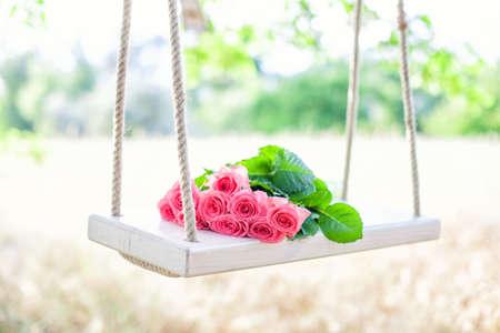 ramo de flores: Flores rosadas hermosas que mienten en un columpio