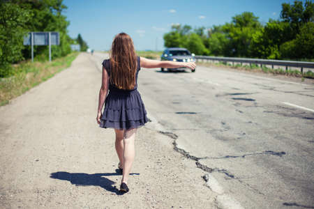 hitch hiker: The girl goes on road and holds a hand