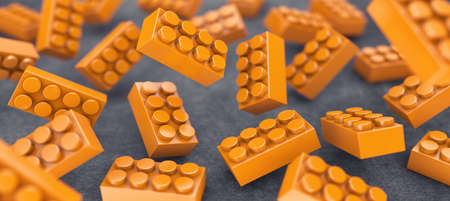 constructor: Many orange constructor chaotically flying in air Stock Photo