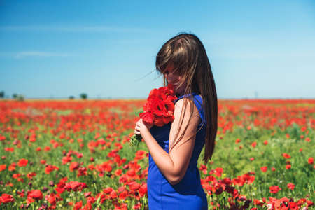 flowers garden: The beautiful girl on a red field with poppies