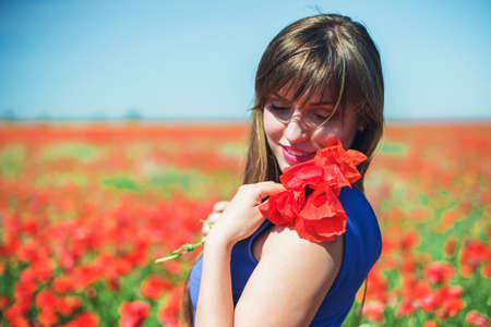 young beautiful woman: The beautiful girl on a red field with poppies