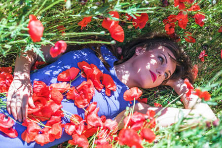 woman in field: The beautiful girl on a red field with poppies