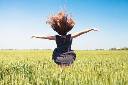 Het mooie meisje is op een tarwe veld Stockfoto