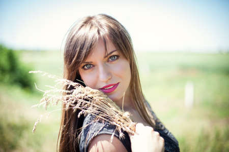 woman in field: Beautiful girl with a bouquet yellow grass Stock Photo