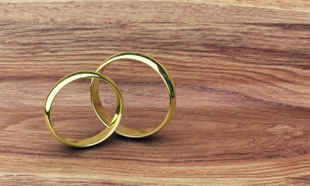 assent: Illustration of two gold rings on a wooden table