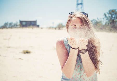 girl blowing: Beautiful girl blowing sand with hands on the beach
