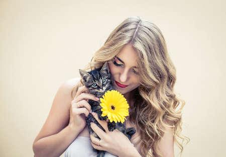 mujeres jovenes desnudas: Hermosa chica con una bonita flor y gato en las manos Foto de archivo