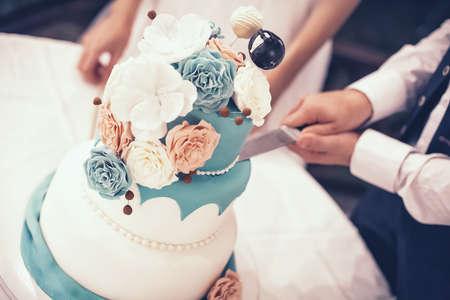 De bruidegom snijdt mooie en grote bruidstaart