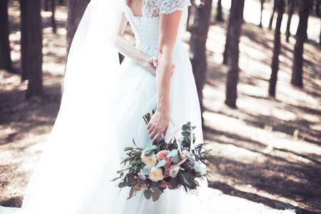 Bruid in een witte jurk en met een mooi boeket