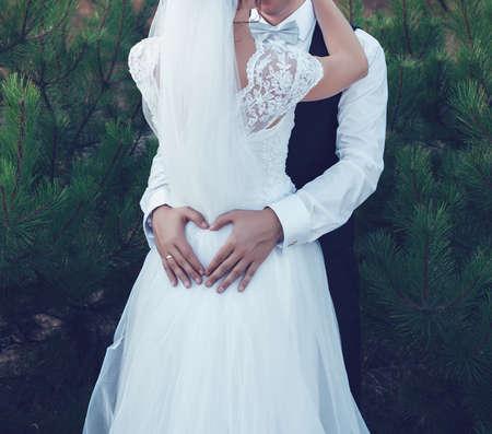 Bruidegom omarmt de bruid twee handen in de vorm van hart Stockfoto