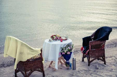Tafel en stoelen op zeekust voor een romantisch afspraakje Stockfoto