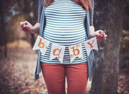 Mooie zwangere vrouw met een grote buik op buitenshuis Stockfoto