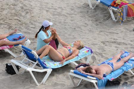 masseuse: Masseuse do the massage on the beach