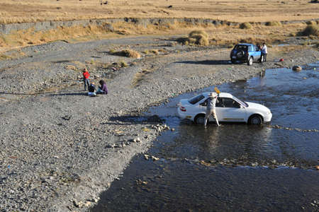 residents: Residents of La Paz wash their cars in a mountain river in urban area.