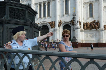femme policier: The policewoman indicates the direction of the tourist. Moscow