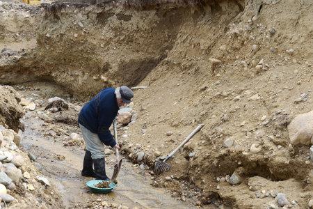 prospector: Minera de oro limpia una roca en el borde de la Tierra.