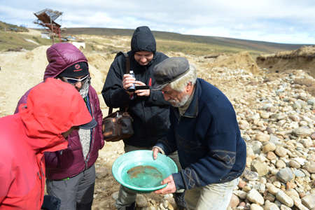 prospector: Gold digger shows tourists alluvial gold sand mined in the mine on the island of Tierra del Fuego.