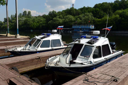 ensuring: Police boats at the dock. Russian police keeps order on the waterways of the country, ensuring safety of vacationers and preventing accidents. Editorial