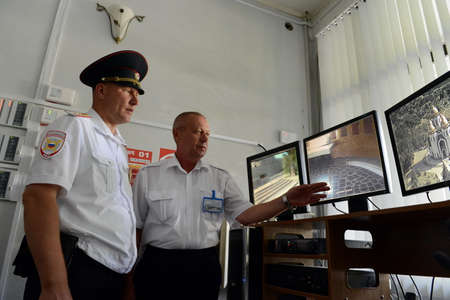 security company: Police officer and security company monitors the cameras control of the territory of Mamayev Kurgan in Volgograd.