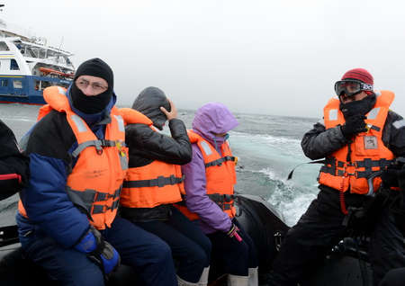 disembark: Tourists disembark from cruise ship Via Australis on Cape horn. Cape Horn - the southernmost point of the archipelago of Tierra del Fuego. Editorial